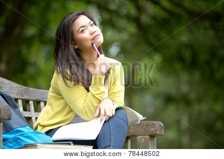 Beautiful young asian university or college student sitting on wooden bench in park, with books and rucksack by side, thinking with pen placed by cheek.