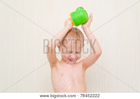 little boy in the bathroom on a white background pour it on his head with a bottle of water