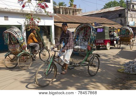 Rickshaws drive by the street in Bandarban, Bangladesh.