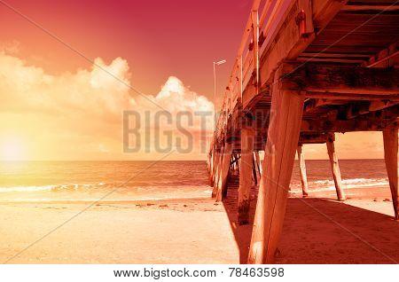 Long Jetty Pier On Wide Open Sandy Beach Overlooking Ocean. Sunset.