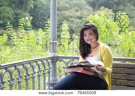 Beautiful young female university or college student smiling while holding a book, seated by a lake in a park.