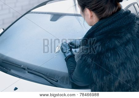 Winter Driving - Woman Scraping Ice from a Windshield