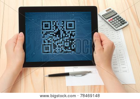 Hands hold tablet PC with QR code