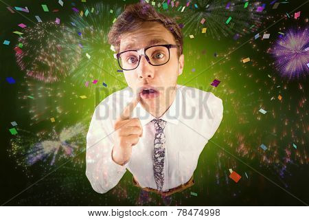 Young geeky businessman looking at camera against colourful fireworks exploding on black background