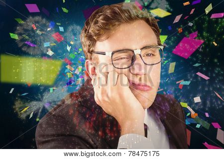 Young geeky businessman looking bored against colourful fireworks exploding on black background