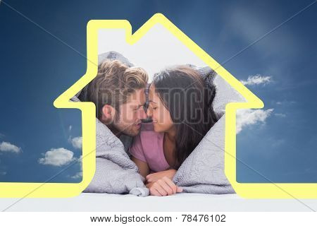 Beautiful couple wrapped in the duvet against cloudy sky with sunshine