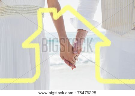 Newlyweds holding hands against house outline