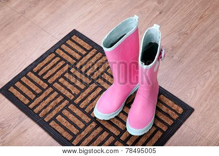 Pink wellington boots on door mat in room
