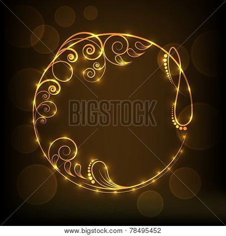 Beautiful rounded frame decorated by golden floral design on brown background.