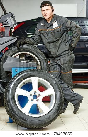 Auto repairman with automobile car wheel at tyre fitting machine during tire replacing