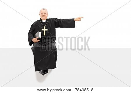 Mature priest pointing with his hand seated on panel isolated on white background