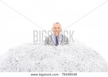 Senior trapped in a pile of shredded paper isolated on white background