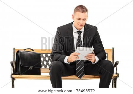 Young businessman working on a tablet seated on a bench isolated on white background