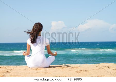 woman on beach meditating