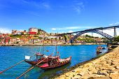 stock photo of bridge  - Oporto or Porto city skyline Douro river traditional boats and Dom Luis or Luiz iron bridge - JPG