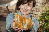 stock photo of fresh slice bread  - Young positive woman offering fresh sliced bread - JPG