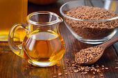 stock photo of flaxseeds  - Brown flax seeds on spoon and flaxseed oil in glass jug on wooden table - JPG