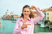 stock photo of piccolo  - Happy young woman framing with hands while standing on bridge with grand canal view in venice italy - JPG