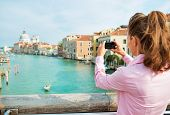 picture of piccolo  - Young woman standing on bridge with grand canal view in venice italy and taking photo - JPG