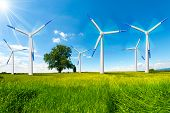 stock photo of turbines  - Six wind turbines in countryside with tree blue sky clouds and sun rays - JPG