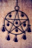 stock photo of pentacle  - Pentagram wind chime with bells hanging against yellow stucco wall - JPG