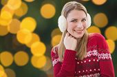 picture of muff  - Woman wearing warm ear muffs against blurry yellow christmas light circles - JPG