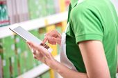stock photo of apron  - Sales clerk wearing apron using a digital tablet with store shelves on background - JPG