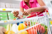 picture of check  - Unrecognizable woman checking a long grocery receipt leaning to a full shopping cart at store - JPG