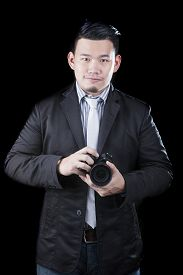 foto of pro-life  - young asian man holding dslr camera take a photography by low key low light white dark background technical use for people activities and human occupation career - JPG