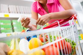 foto of grocery cart  - Unrecognizable woman checking a long grocery receipt leaning to a full shopping cart at store - JPG