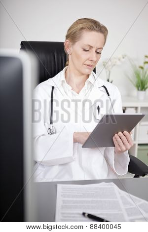 Sitting Woman Doctor Browsing At Tablet Computer