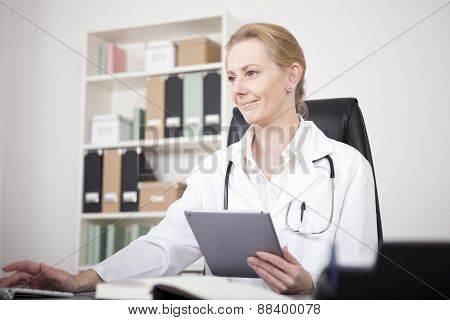 Doctor Using Tablet And Desktop Computer Together