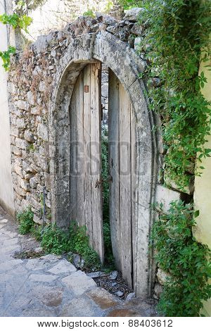 the old door against an overgrown stone wall