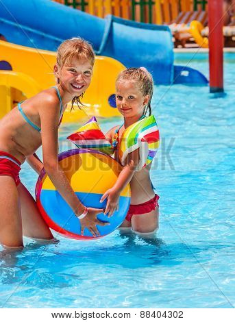 Child on water slide at aquapark. Summer holiday. Beach ball.