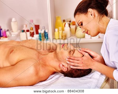 Man getting facial  massage in beauty spa. Hand on head.