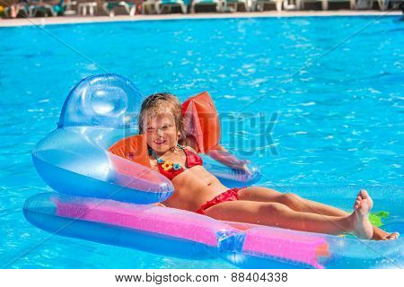 Little girl swimming on inflatable beach mattress. Armbands on hand