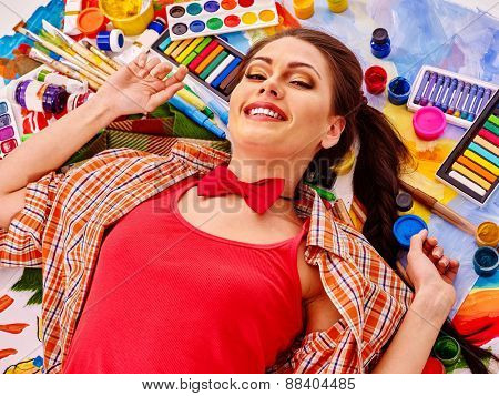 Artist woman lying on paint palette. Red t-shirt.