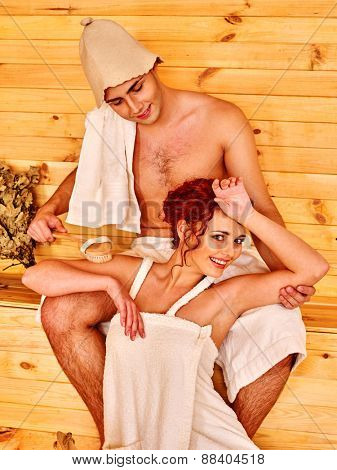 Group people in hat  relaxing at sauna. Loving couple.