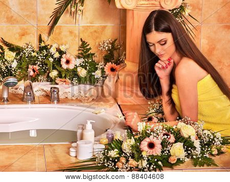 Woman relaxing at water spa. Bathroom in all flowers.