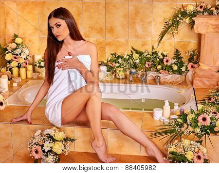 Woman relaxing at water spa. On steps of many colors.