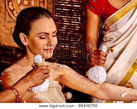 Woman having ayurvedic massage with pouch of rice. Indian culture.