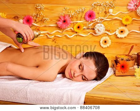 White woman getting  massage in wooden spa. Pouring oil.
