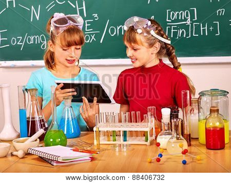 Child holding tablet pc in chemistry class. Blackboard background.