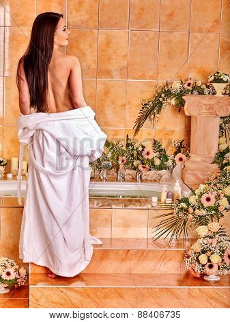 Woman relaxing at water spa. Girl climbs stairs.