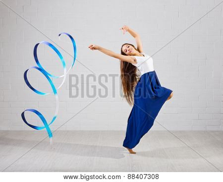 Girl engaged art gymnastic on grey wall