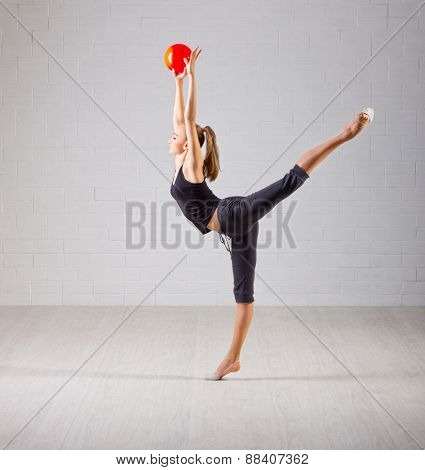 Young girl engaged art gymnastic on grey wall background
