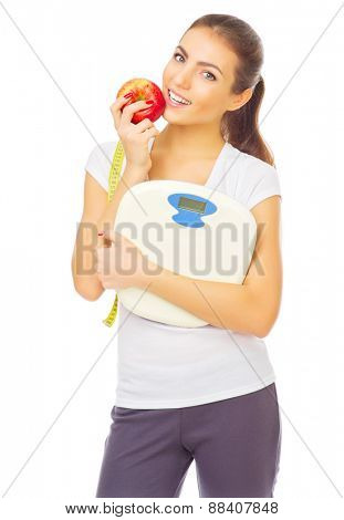 Young healthy girl with scales and apple isolated