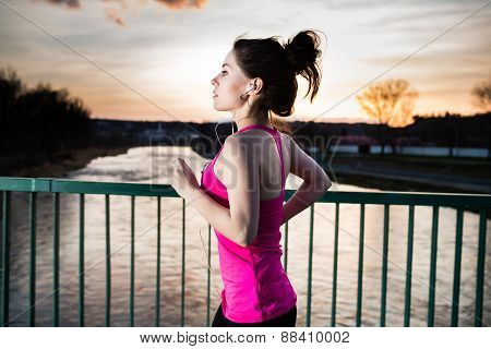 Young woman jogging at sunset