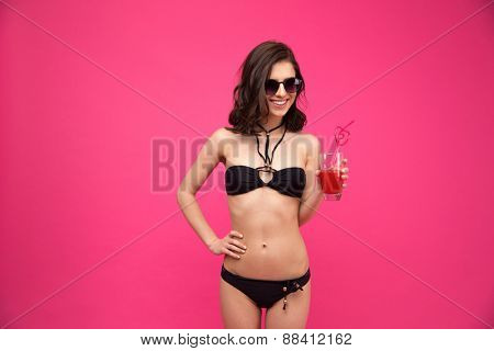 Smiling young woman in swimsuit and sunglasses holding glass of fresh juice