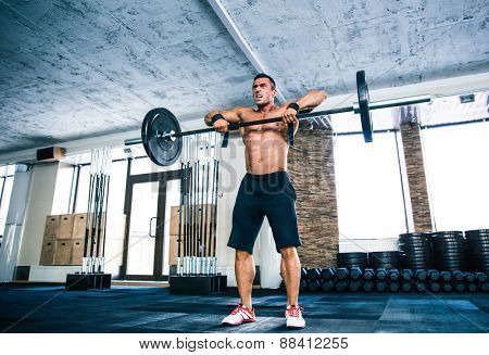 Full length portrait of a muscular man lifting barbell at gym